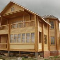Дом из клееного бруса с несколькими балконами и эркером